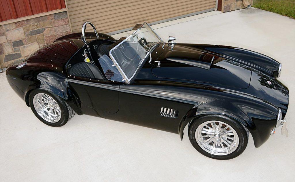 elevated broadside (passenger side) shot of Onyx Black Superformance 427 Shelby classic Cobra street version Roadster for sale, SPO1869