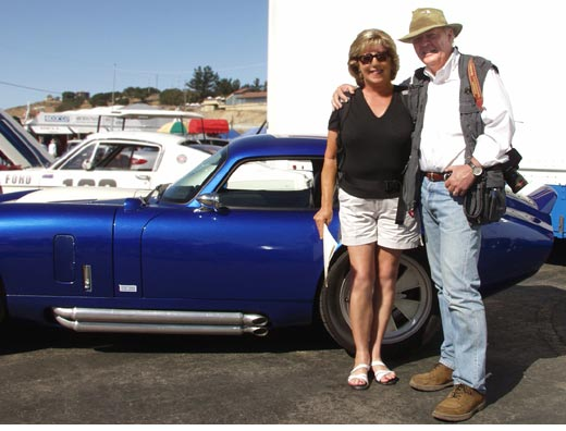 Judy Scott and Peter Brock at Monterey Historic Races/Shelby Spectacular, Laguna Seca, California, 2003. Daytona Coupe for backdrop. Photo by Curt Scott