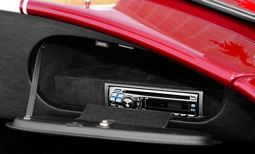glovebox-concealed radio & CD player closeup of Sunset Red Superformance 427SC Cobra for sale by owner, SPO2198