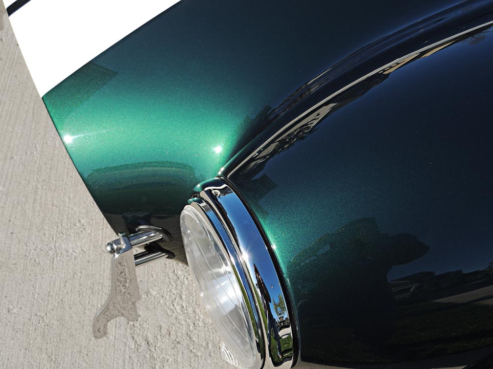 closeup photo of headlamp and paint finish in this Malachite Green Superformance 427SC Cobra for sale, SPO1310