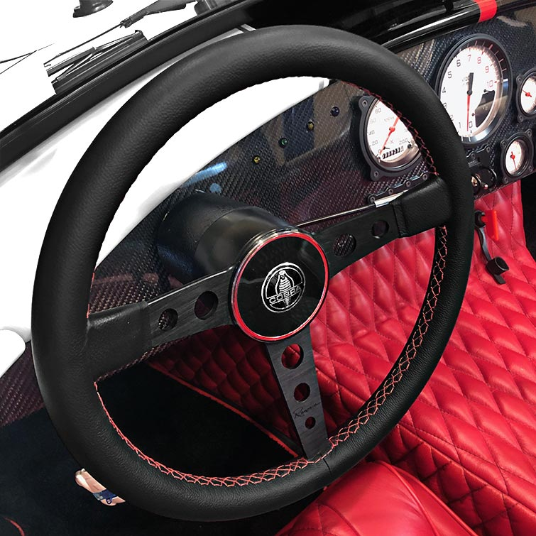 closeup of leather-wrapped steering wheel onf Backdraft Racing replica Shelby classic 427SC Cobra vehicle for sale, BDR#1597. White with black livery.