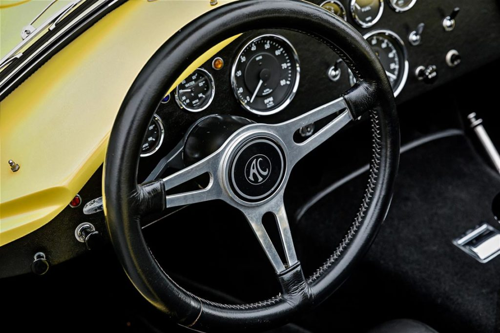 closeup shot of leather-bound steering wheel and dash on Jasmine Yellow Superformance 427SC Shelby Roadster (Street Version) Cobra vehicle for sale, SPO1076