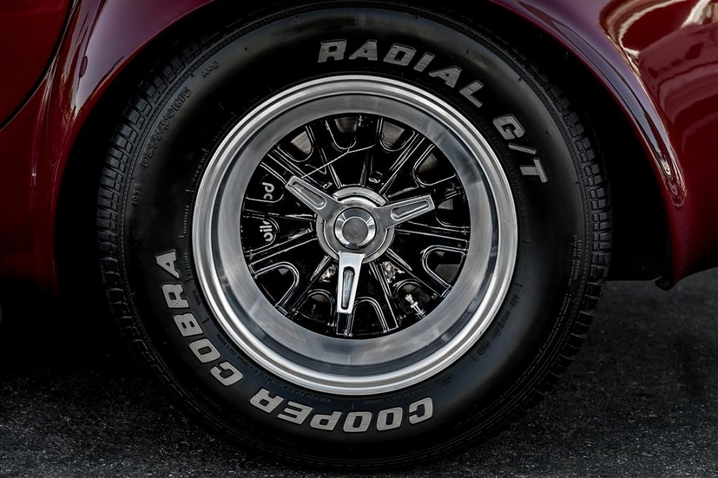 closeup of Halibrand wheel and Goodyear Cobra Radial G/T tire on Sunset Red Superformance Shelby 427SC Cobra for sale