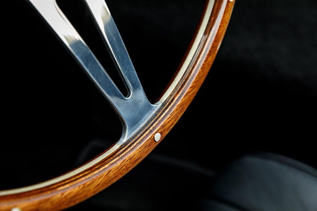 closeup/macro shot of hardwood rim of steering wheel on black-on-black Superformance 427SC Cobra for sale, SPO3367