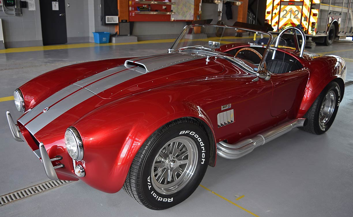 3/4-rear shot (driver side) of Sunset Red Superformance 427SC Shelby classic Cobra for sale, SPO2249